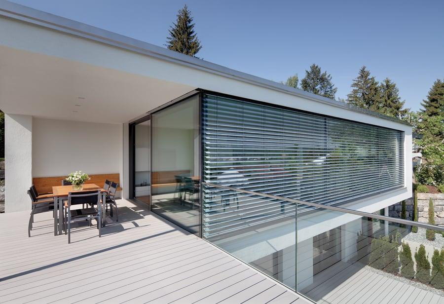 Dům z betonu s velkou prosklenou plochou a předokenní rolety