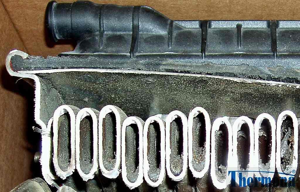 Trubková spirála výměníku kondenzačního kotle zanesená kalovými usazeninami