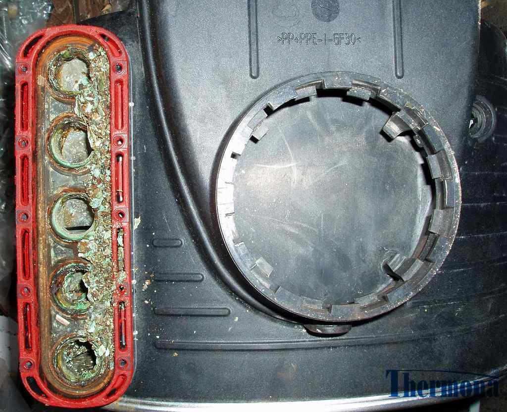 Výměník kondenzačního kotle zanesený nečistotami z topné vody